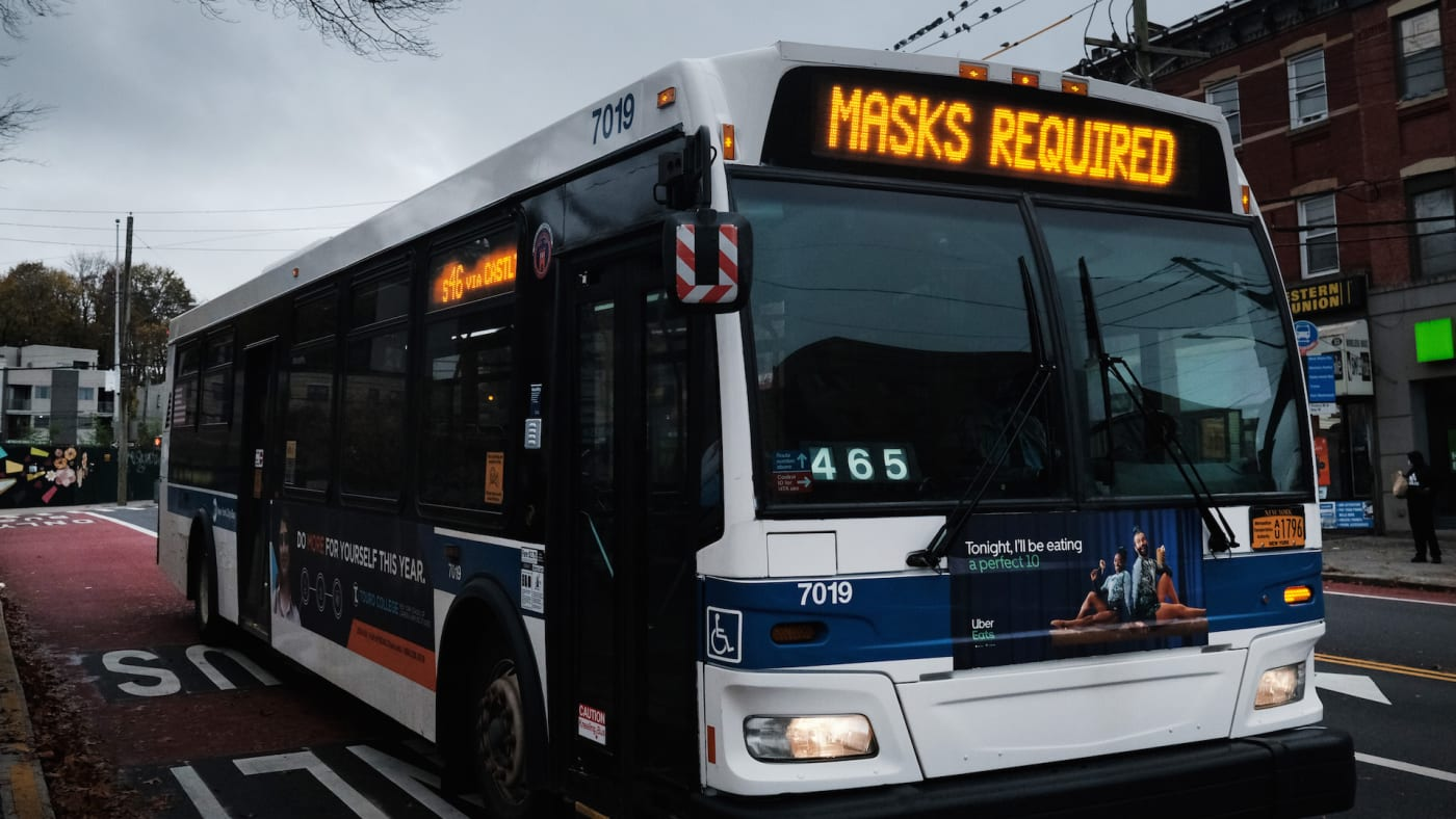 A bus displays a message noting masks are required to board