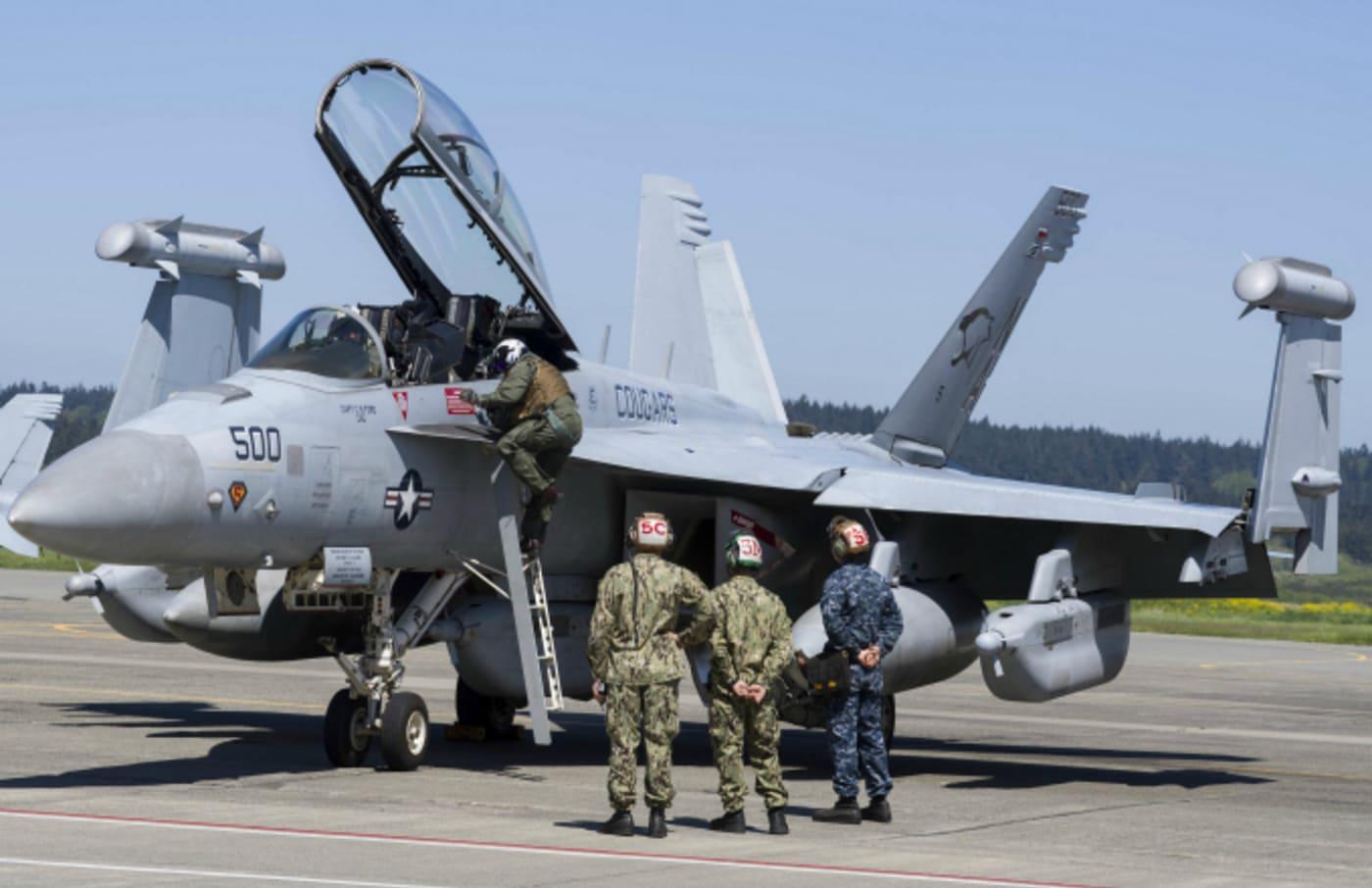 Three technicians watching as pilot climbs to his EA 18G Growler aircraft