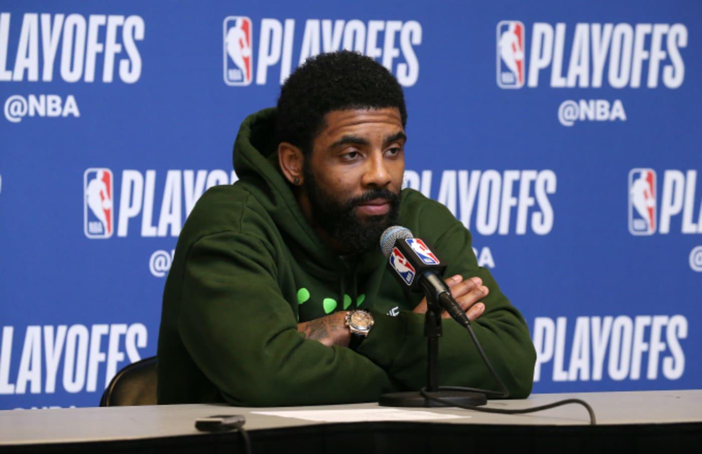 Kyrie Irving #11 of the Boston Celtics speaks to the media