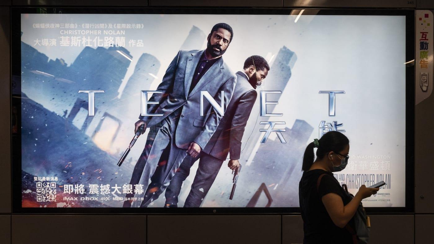 A commuter walks past a poster of Christopher Nolan's blockbuster film Tenet
