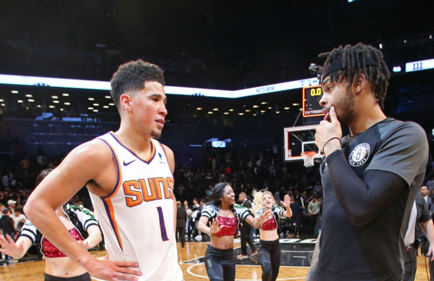 Devin Booker #1 of the Phoenix Suns talks with D'Angelo Russell