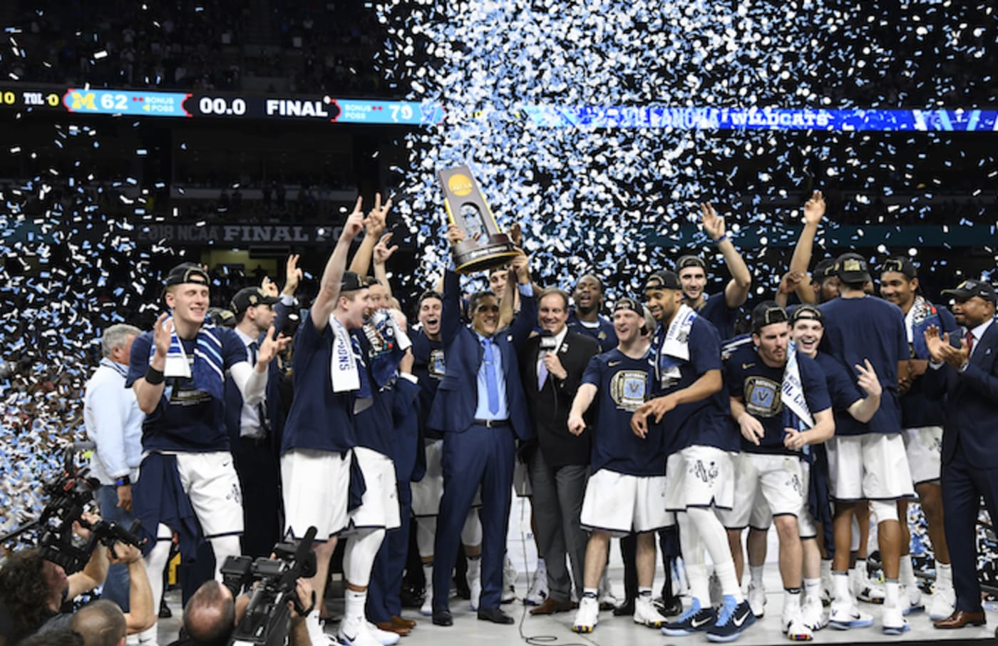 Villanova coach Jay Wright victorious, holding up National Championship trophy with players.
