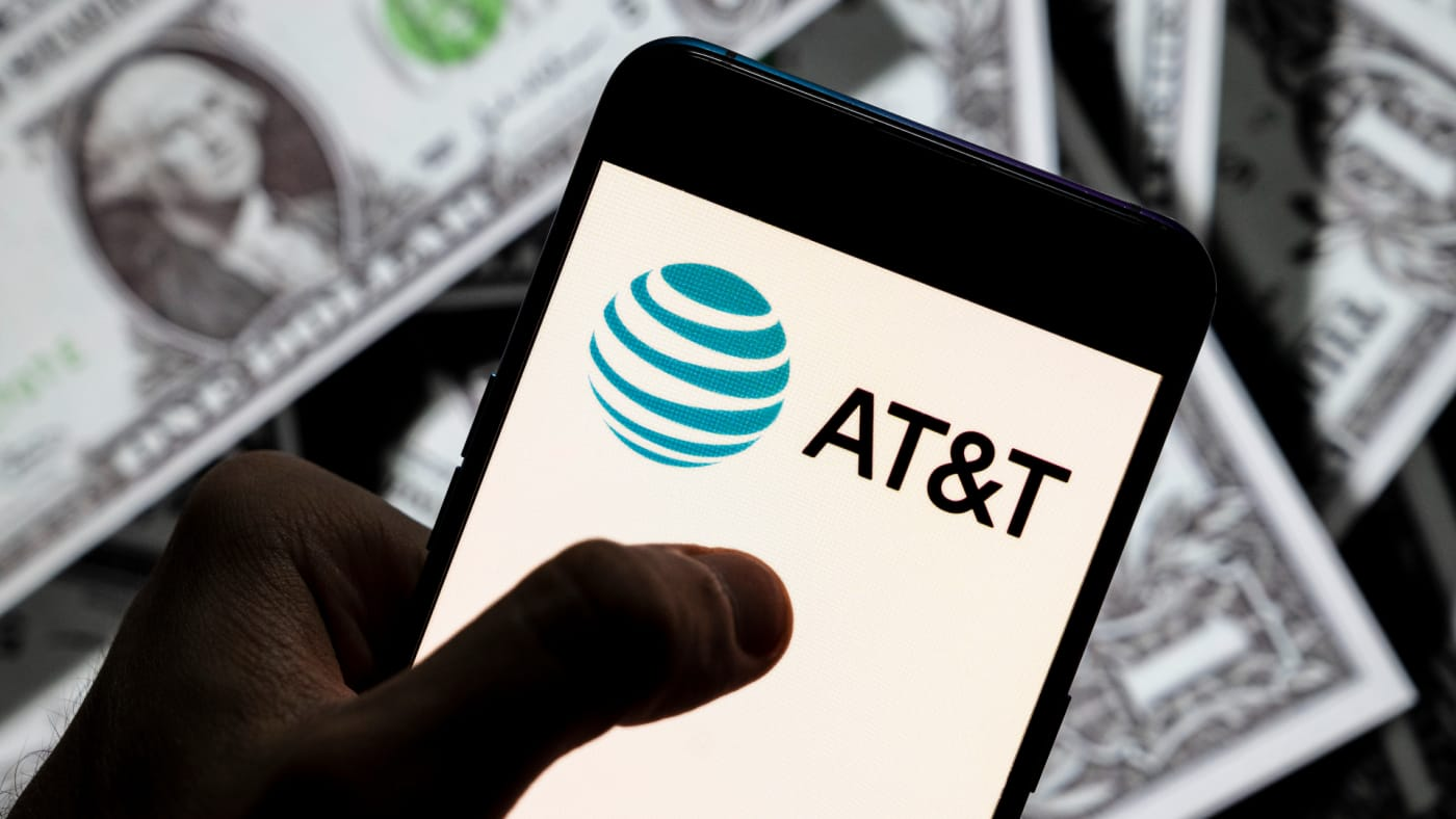 In this photo illustration, an AT&T logo seen displayed on a smartphone with USD (United States dollar) currency in the background.