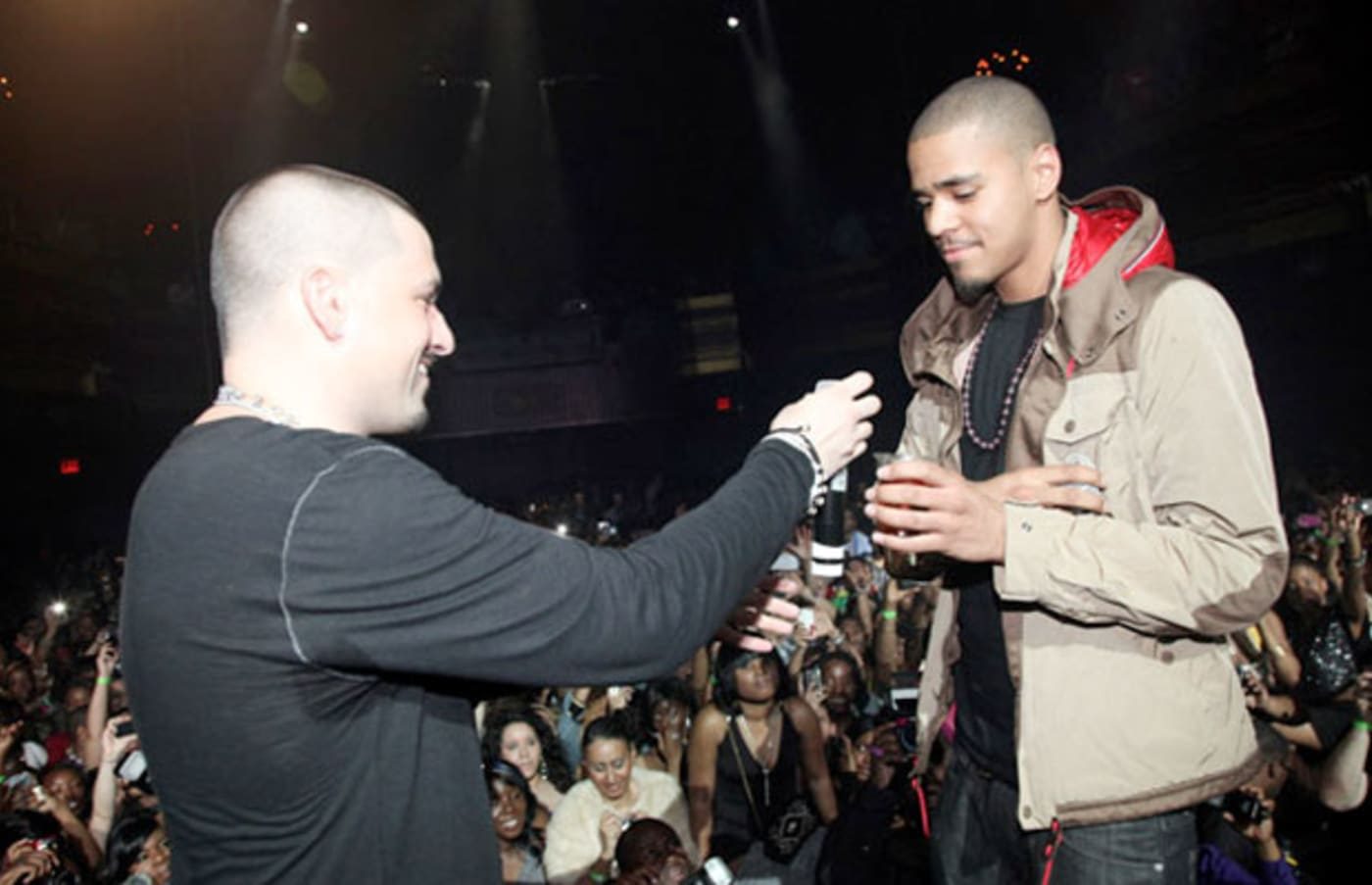 J Cole receiving a microphone