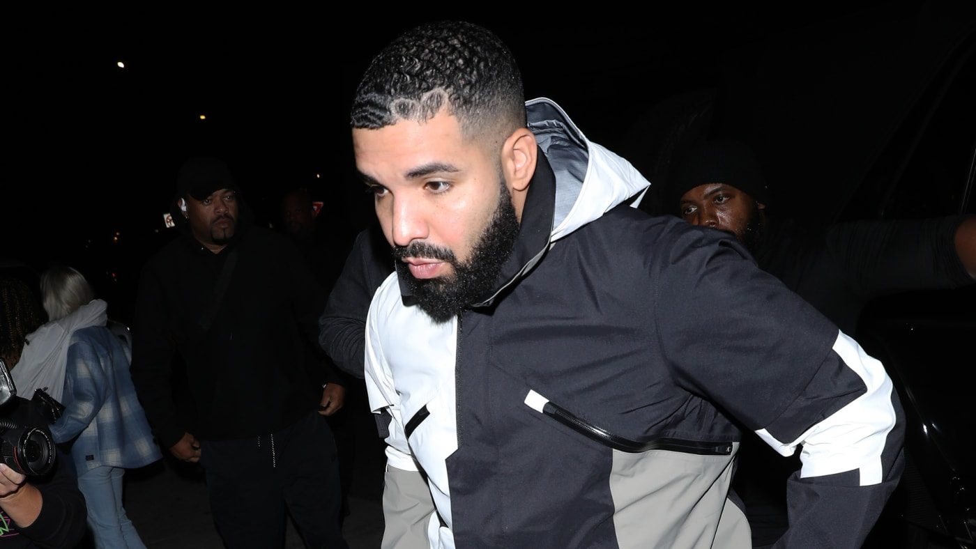 Drake walks into the night as paparazzi descends upon him.