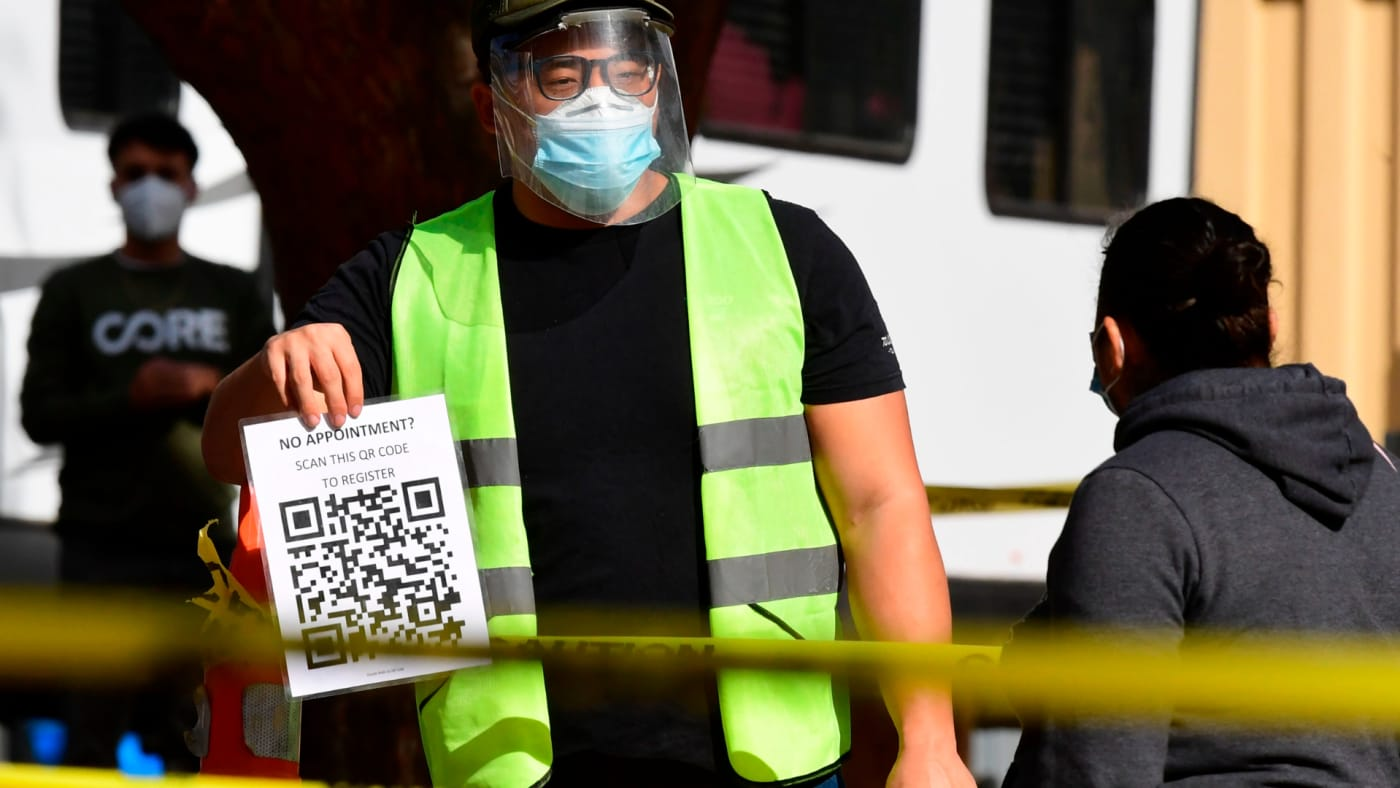 A testing center worker displays a copy of QR code for cellphone scanning of appointments.
