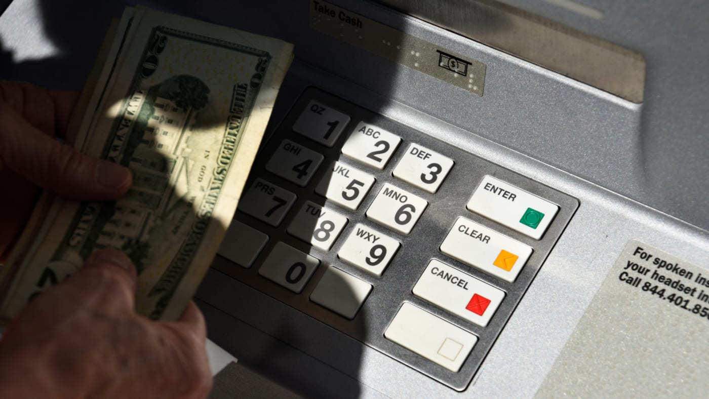 A banking customer withdraws money from a ATM machine.