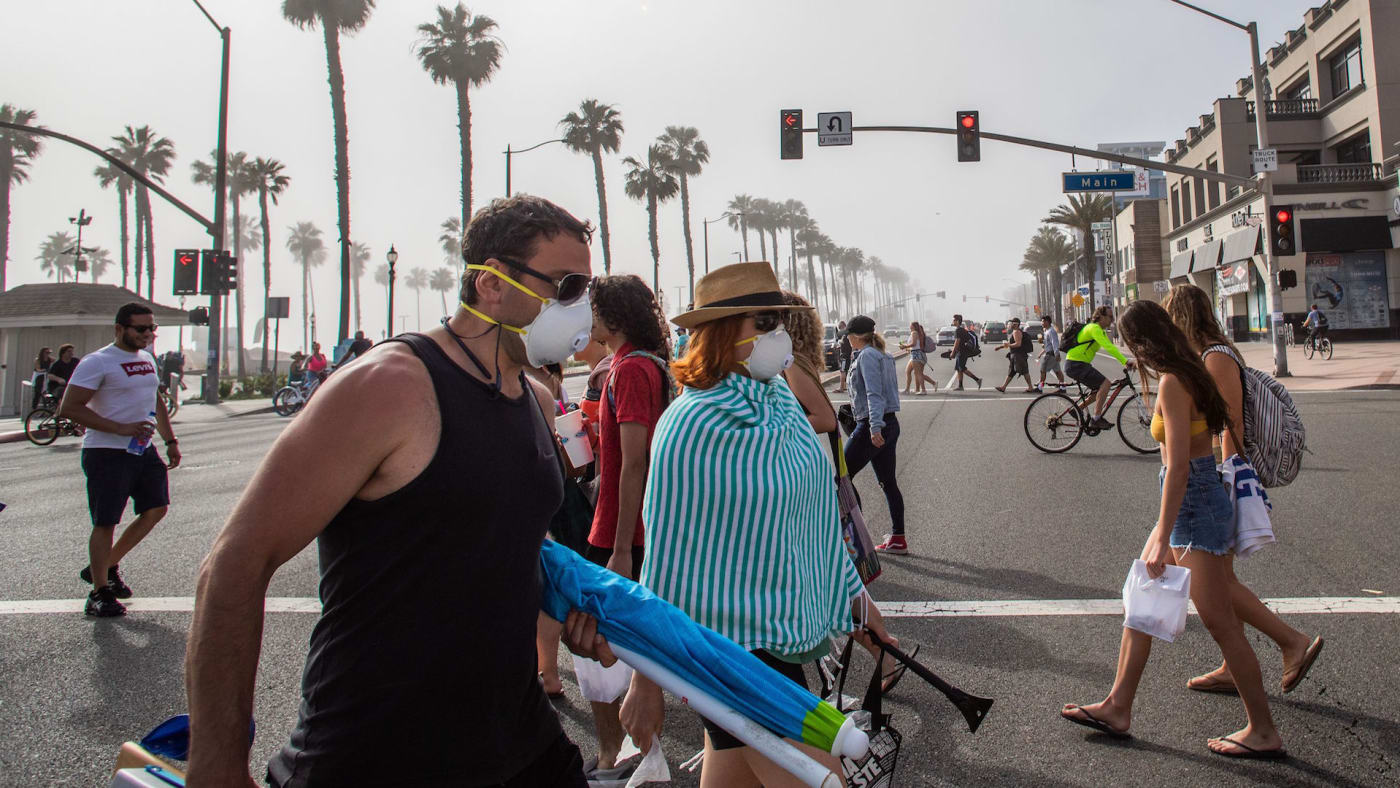 People cross the street amid coronavirus pandemic in Huntington Beach, California
