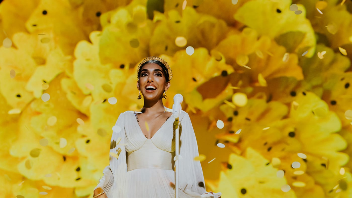Rupi Kaur standing in front of a yellow flower