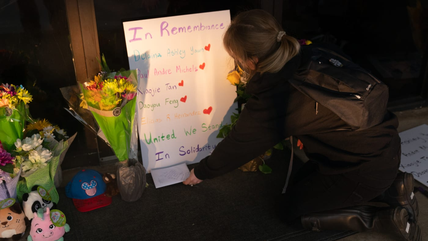 Shelby Swan places sign outside Youngs Asian Massage where four people were shot and killed.