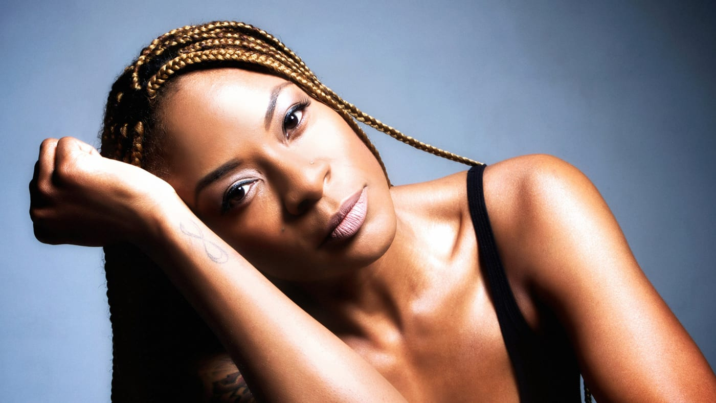 Singer Jully Black posing with her head resting on her arm