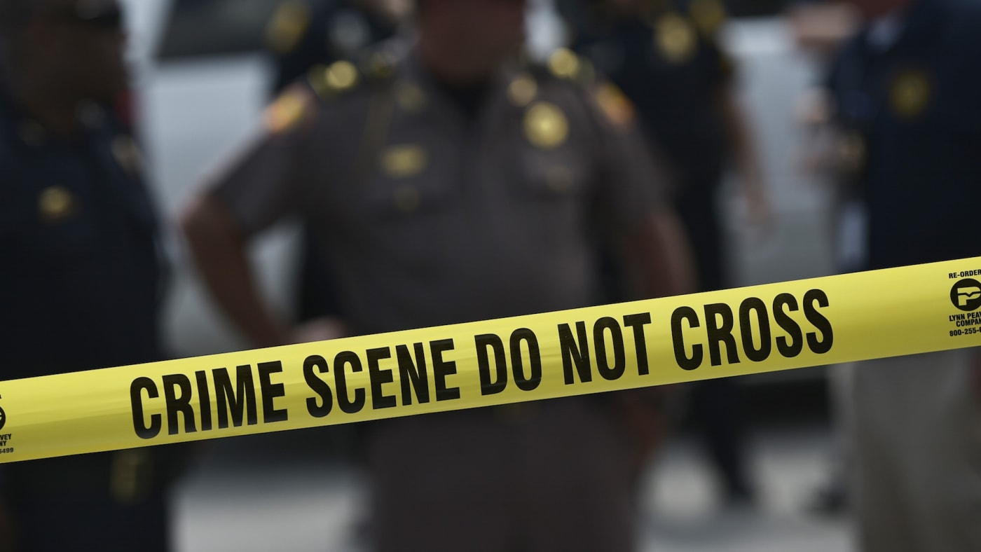 Police stand behind a crime scene tape