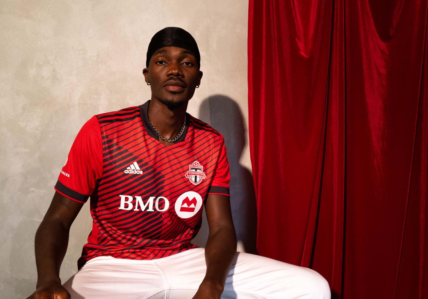 Tobi posting in a red Toronto FC jersey