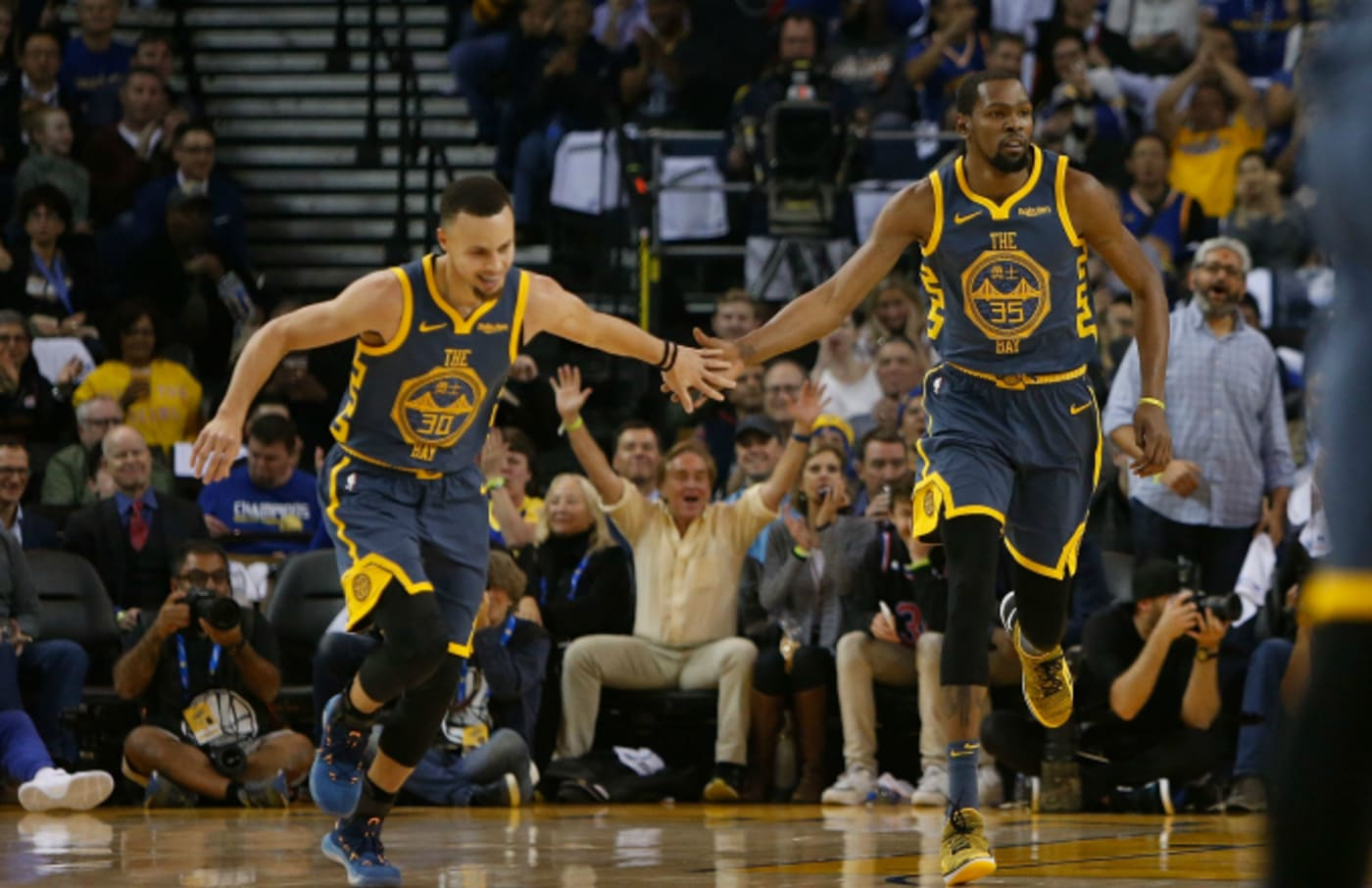 Stephen Curry #30 and Kevin Durant #35 of the Golden State Warriors celebrate a basket
