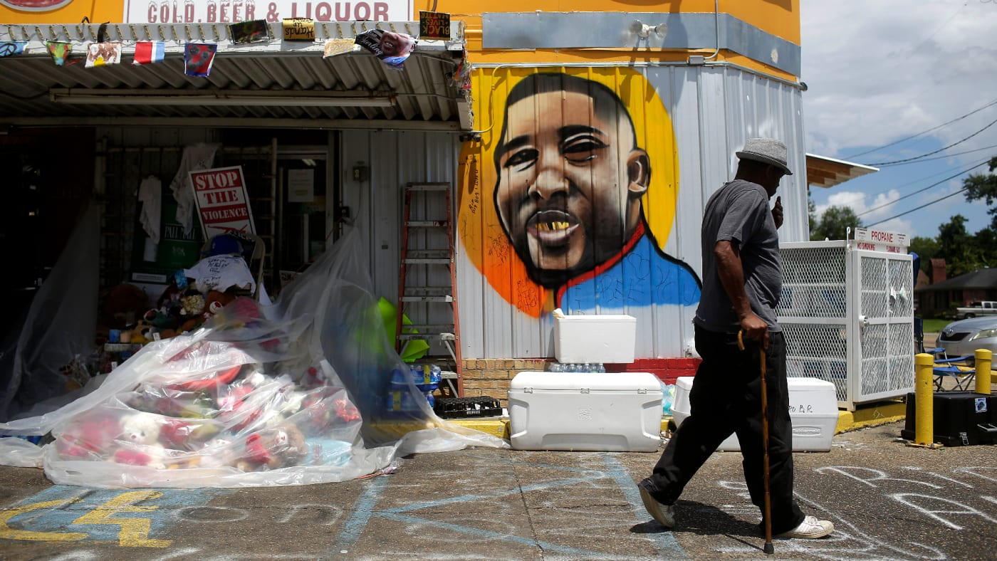 A man walks past a mural of Alton Sterling outside the Triple S Food Mart.