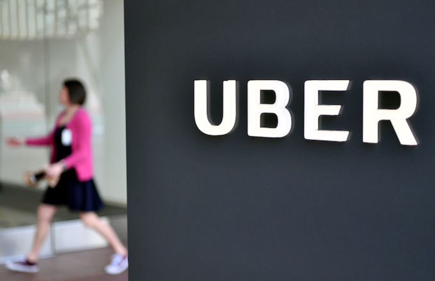 A woman walks into the Uber Corporate Headquarters building in San Francisco, California.