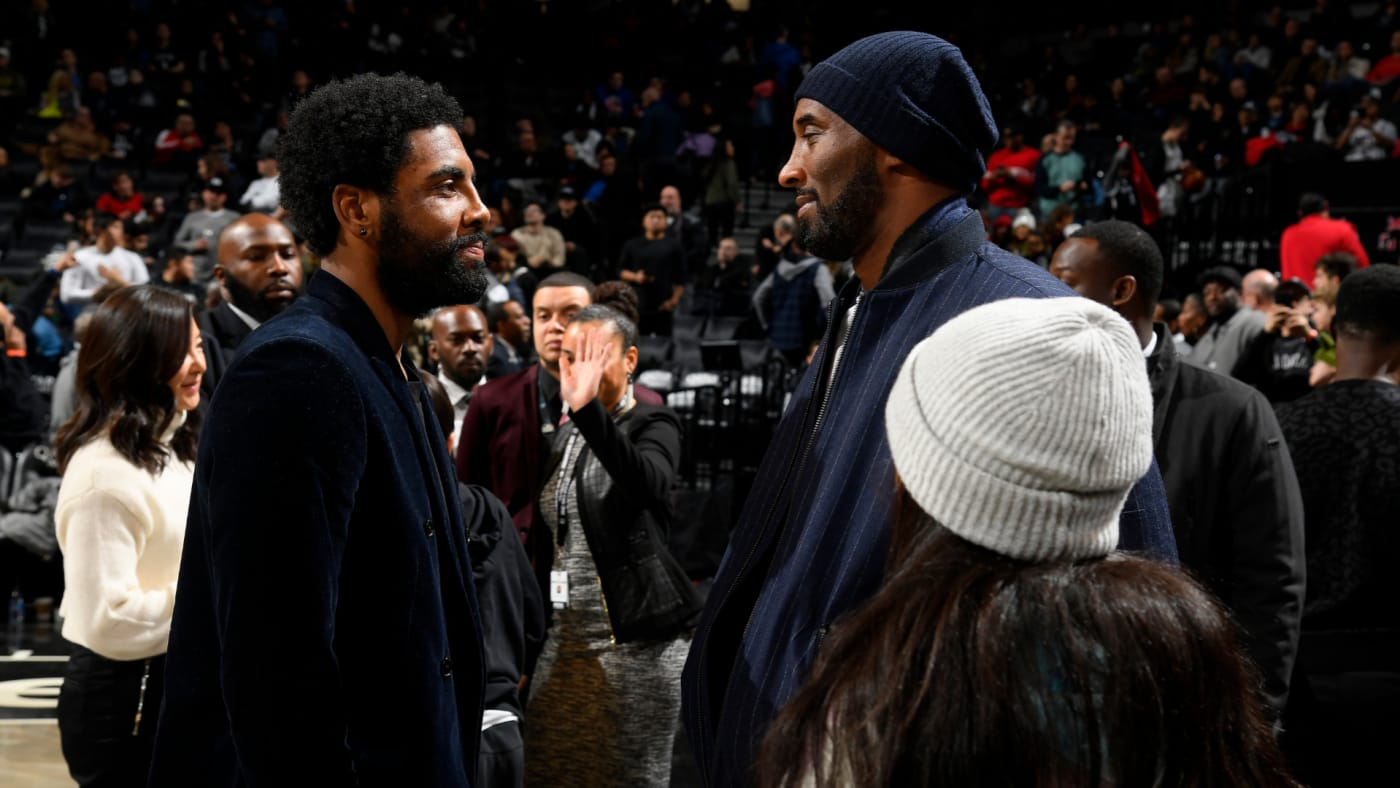 Kobe Bryant talks with Kyrie Irving during the game against the Atlanta Hawks.