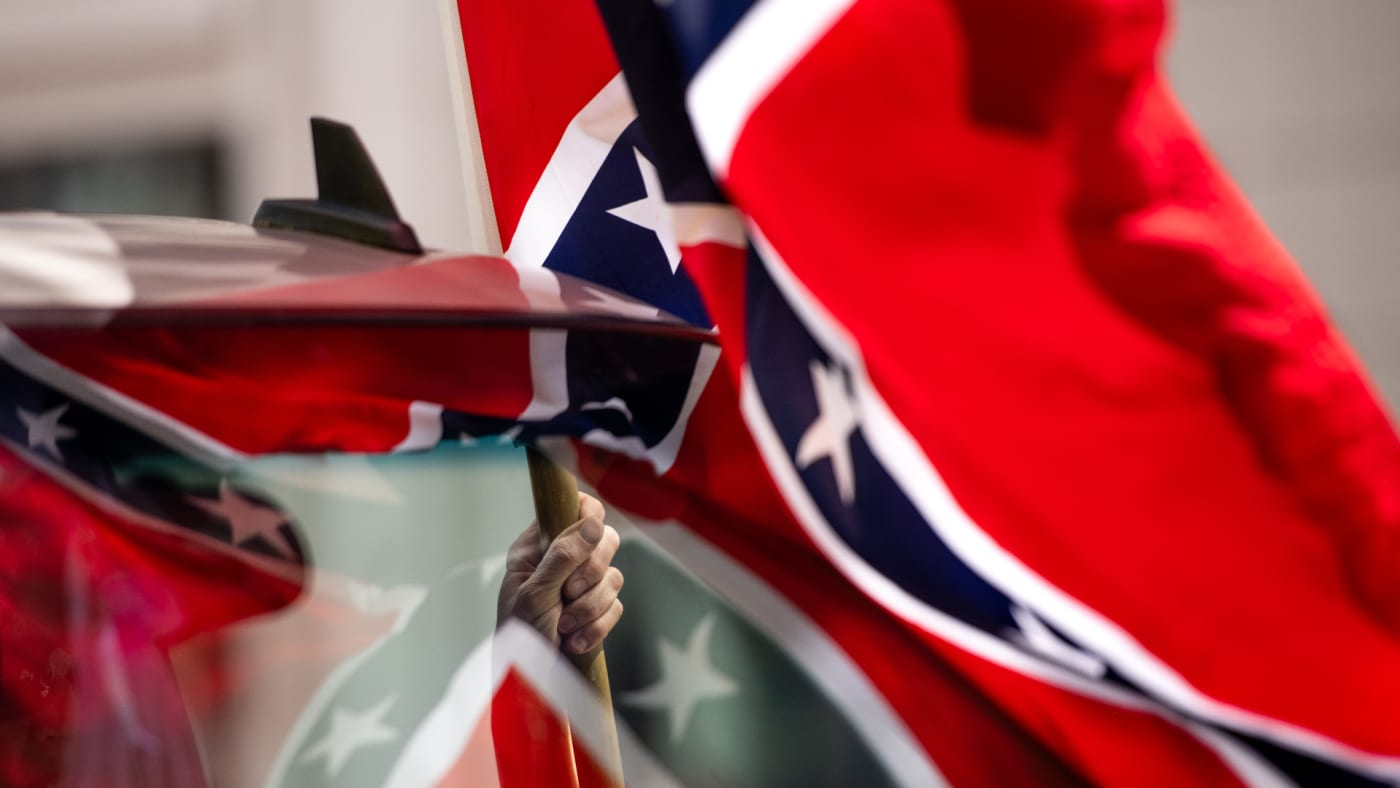 A man holds a Confederate flag while participating in a protest.