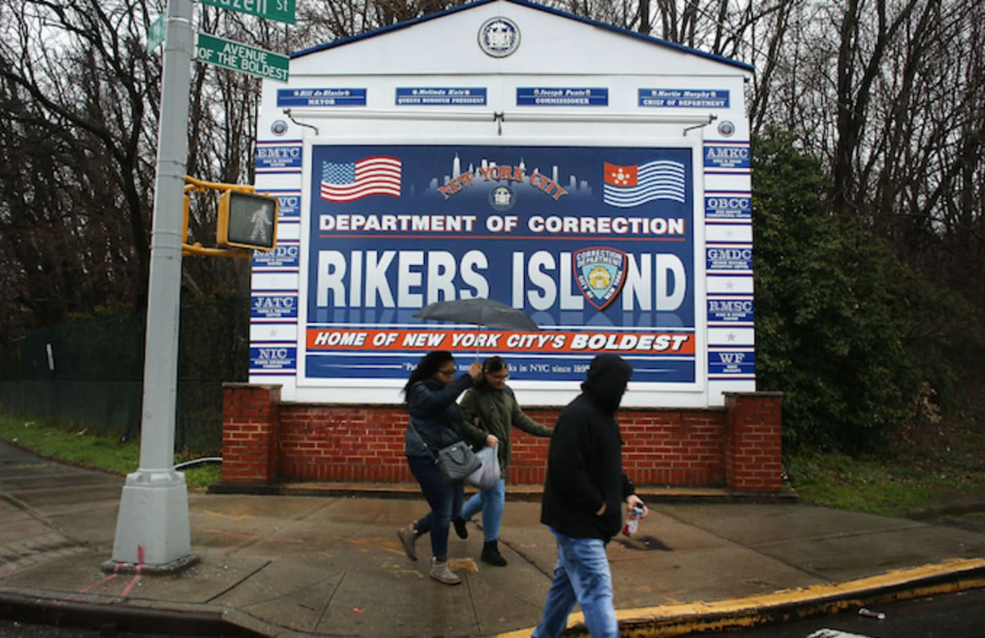 People walk by a sign at the entrance to Rikers Island