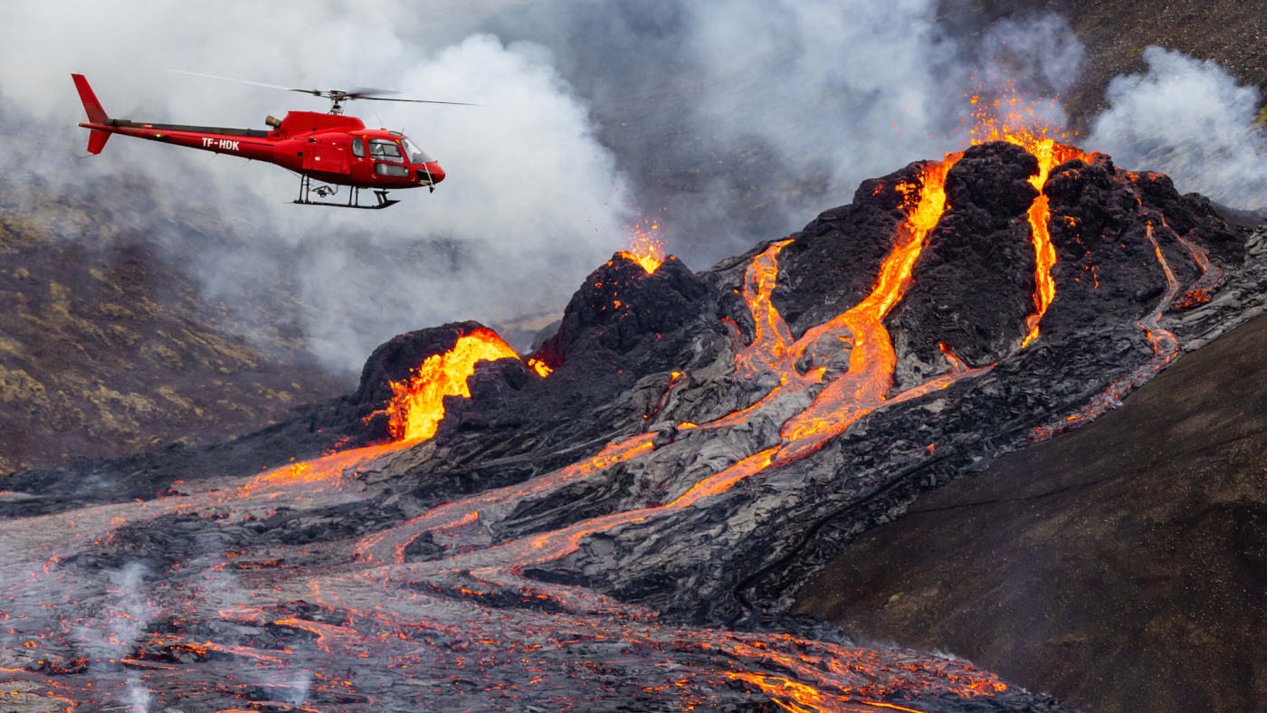 A helicopter flies close to a volcanic eruption