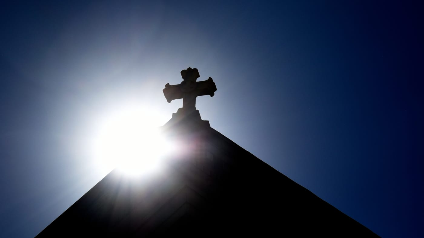 The sun rises behind a stone cross atop the historic Cathedral Basilica of St. Frances of Assisi.