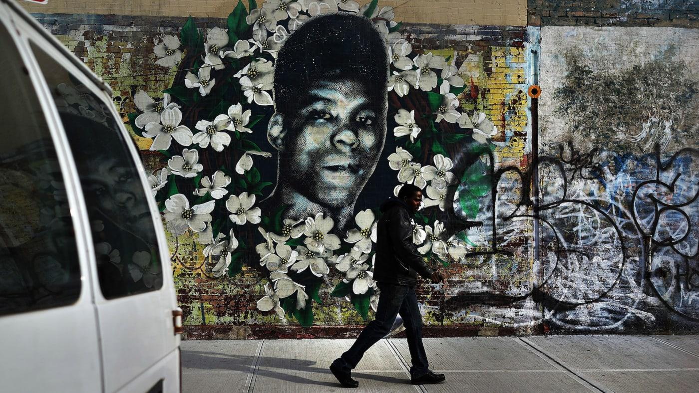A man walks by a walks by a graffiti memorial in memory of Yusef Hawkins.