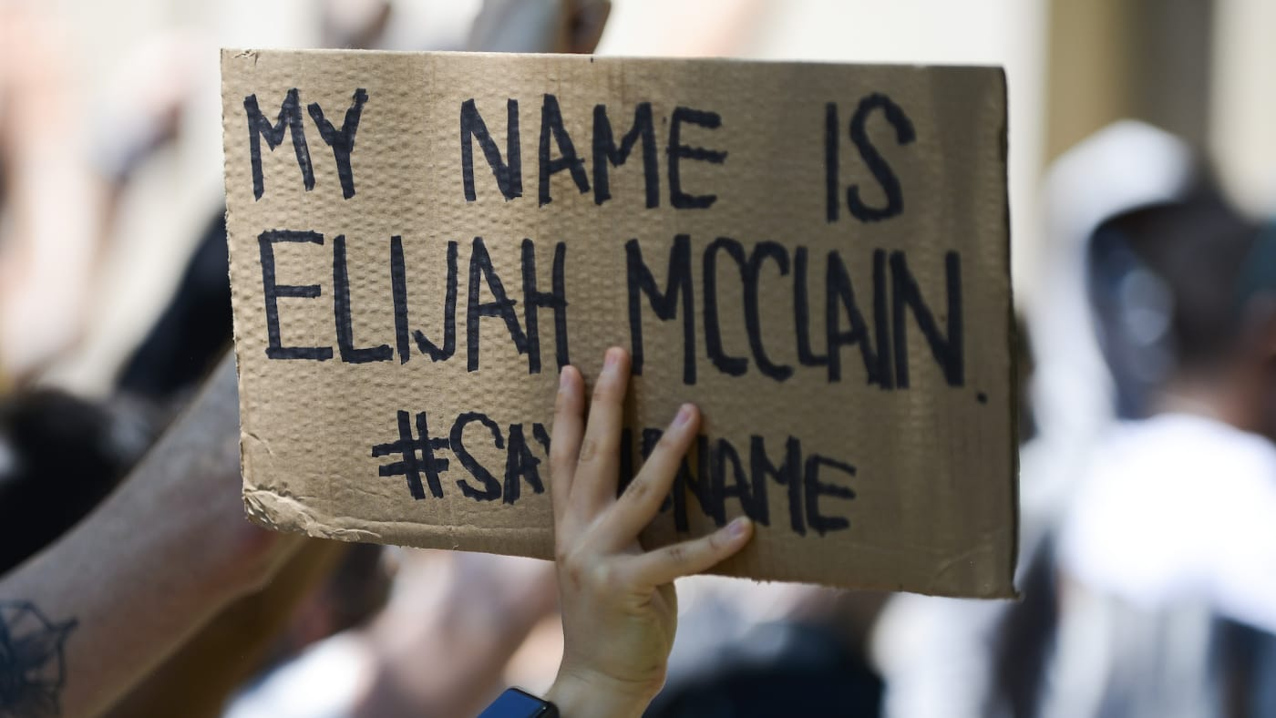 A woman holds sign during rally to demand justice for Elijah McClain.