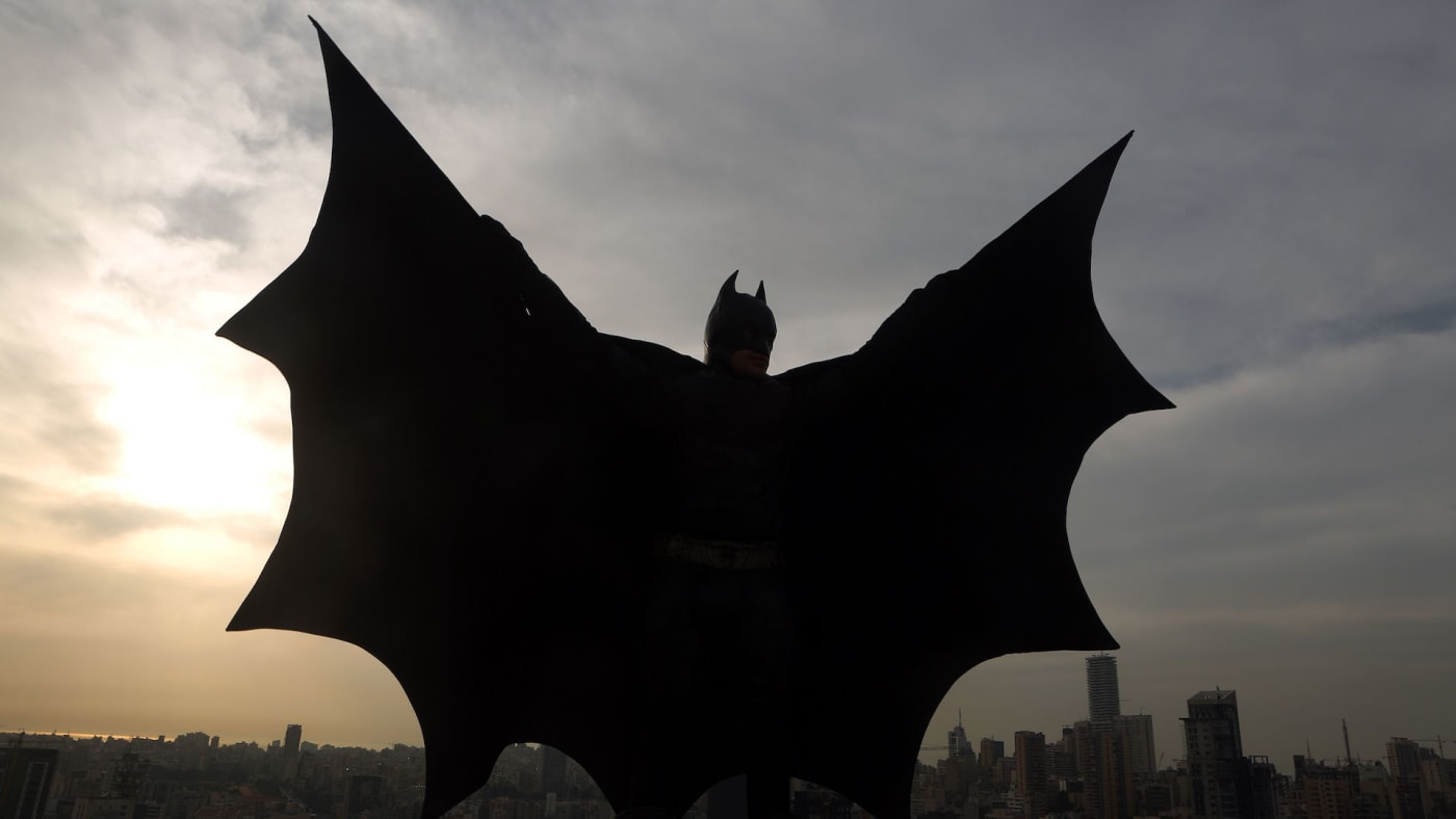 Lebanese model dressed as Batman on rooftop of building during a photoshoot in Beirut.