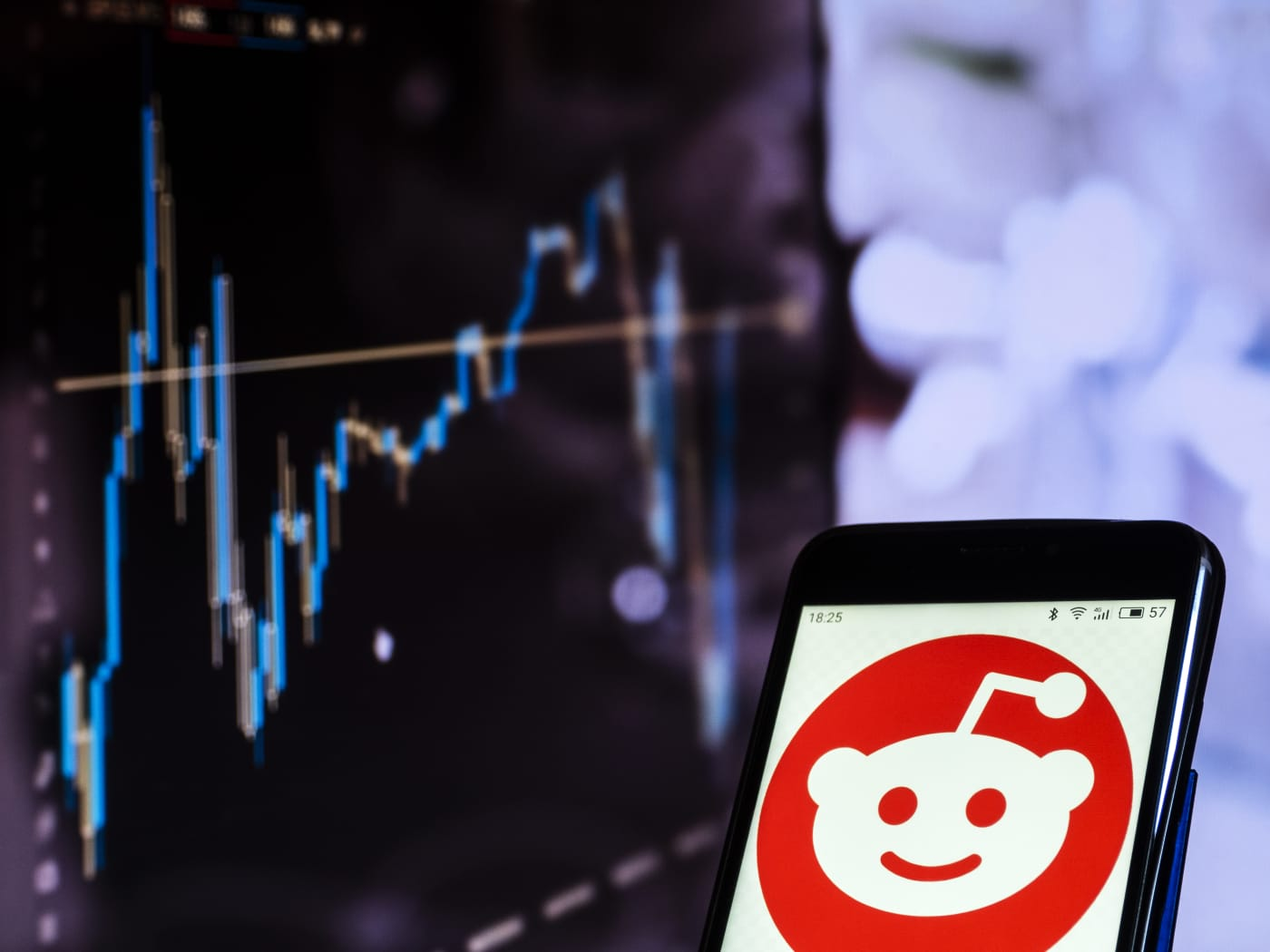 The Reddit logo on a phone screen, in front of a computer screen with a graph on it.