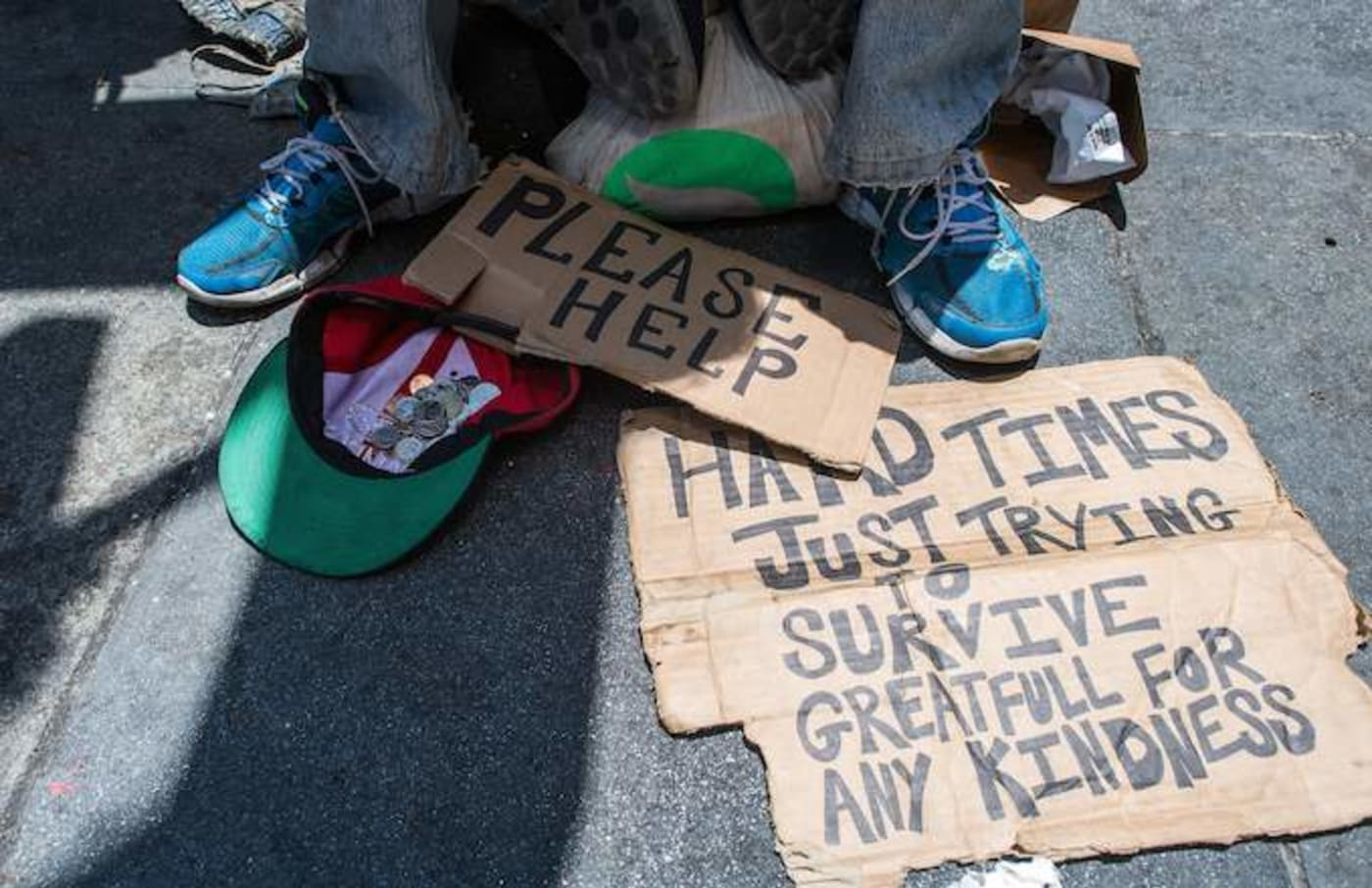 Homeless person begs along a sidewalk in downtown San Francisco
