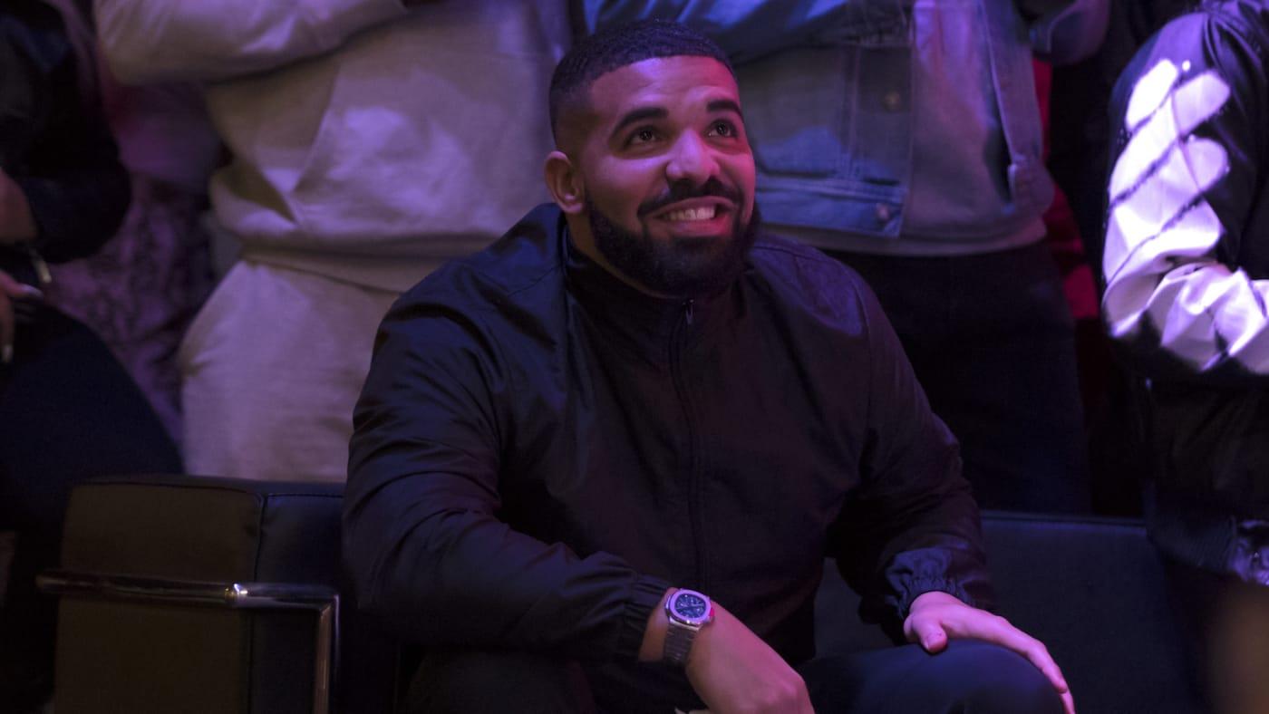 Drake watches a screen alongside other Toronto Raptors fans.