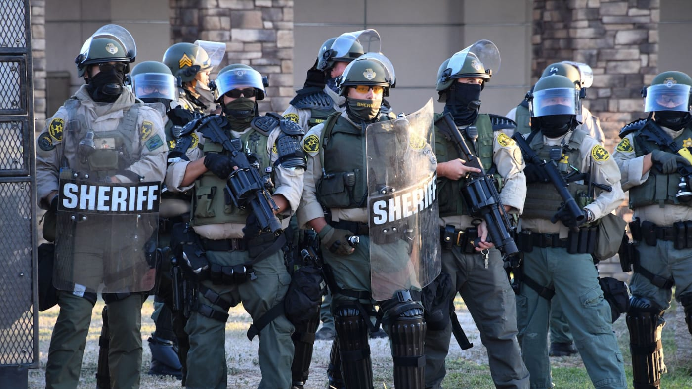 Sheriff's in riot gear stand in front of the South L.A. Sheriff's Station