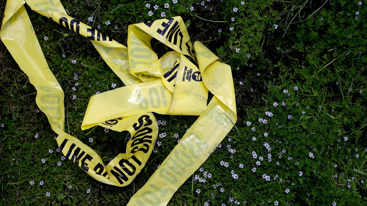 Yellow police crime scene tape rests in the grass on July 19, 2016 in Baton Rouge, Louisiana.