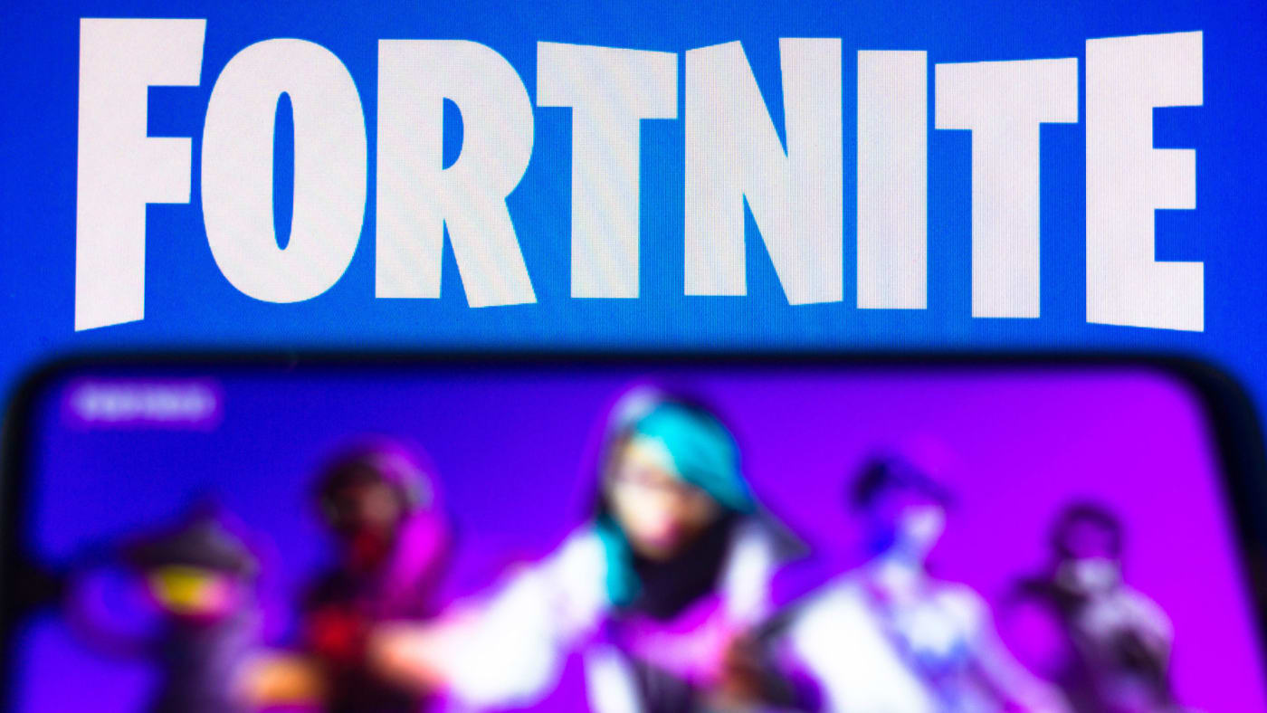 The Fortnite logo is seen on a smartphone and a PC screen.
