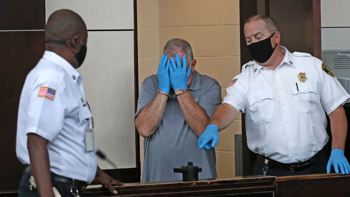 Patrick Rose covers his face during his arraignment at Boston Municipal Court in August 2020.