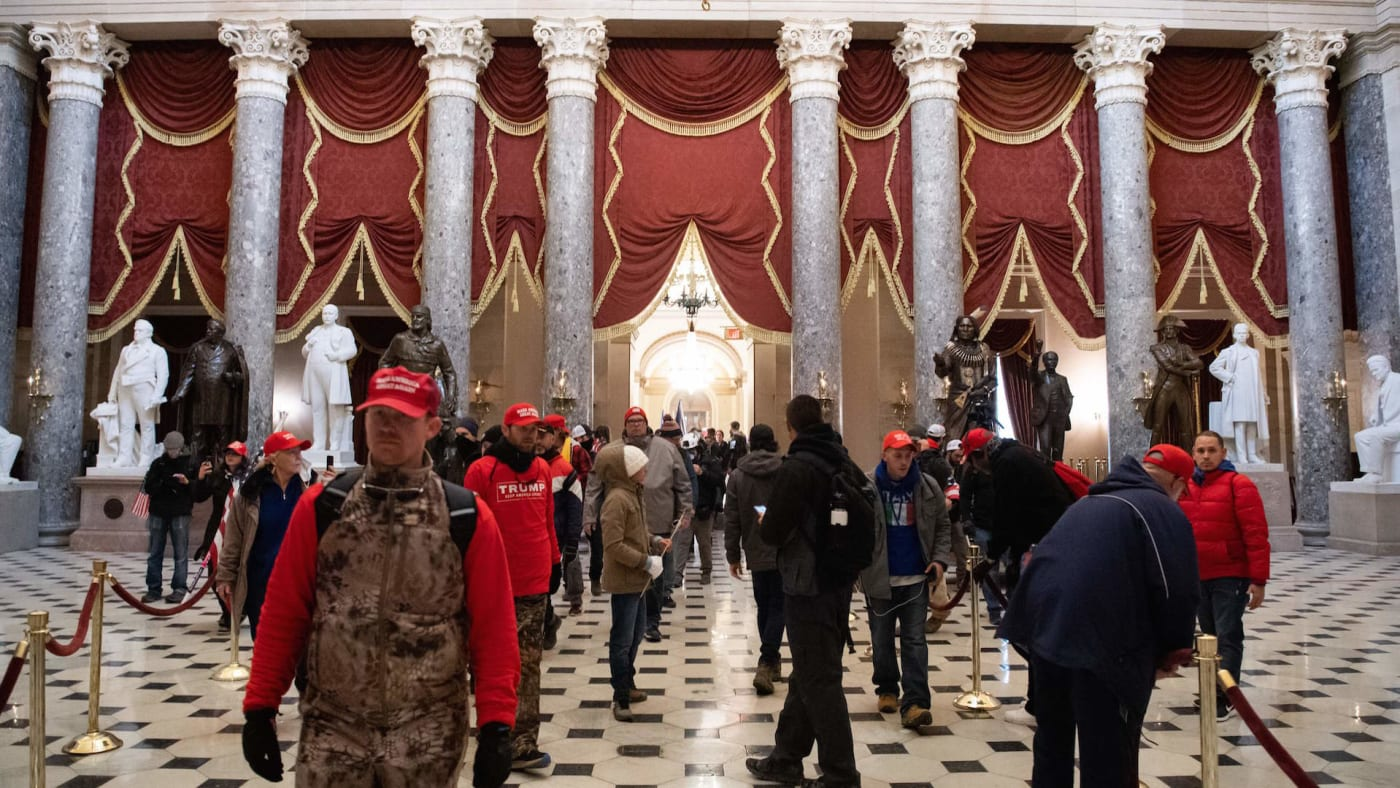 Supporters of US President Donald Trump walk through Statuary Hall