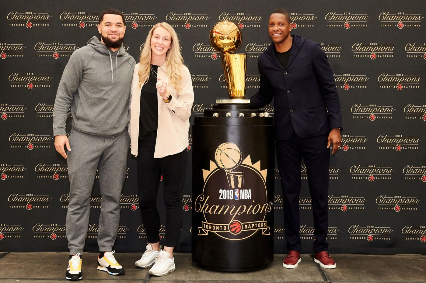 Toronto Raptors' Shelby Weaver poses with Fred VanVleet, Masai Ujiri, and the Larry O'Brien trophy