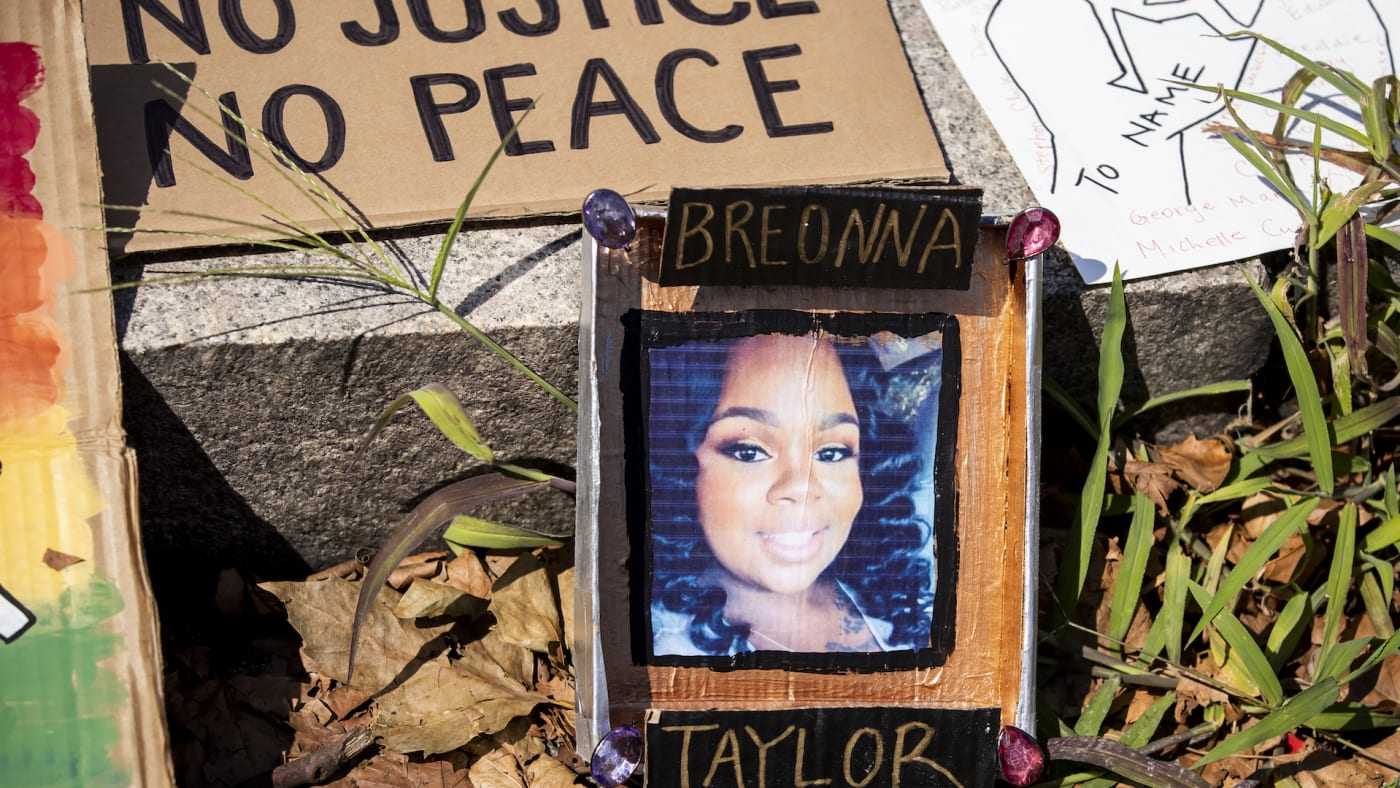 A line of homemade protest signs lay on the steps including one with a picture of Breonna Taylor.