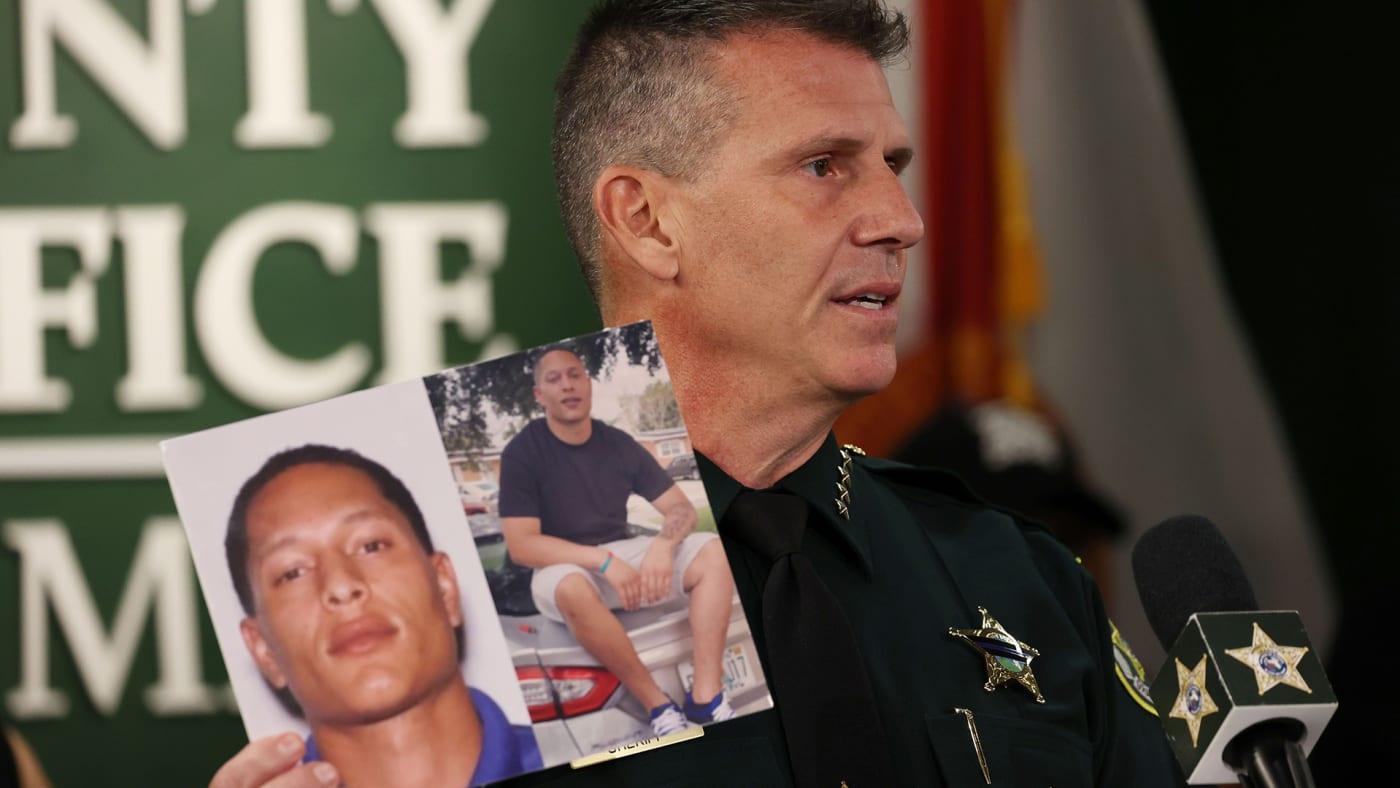 Sheriff John W. Mina shows photos of Armando Manuel Caballero during a press conference.