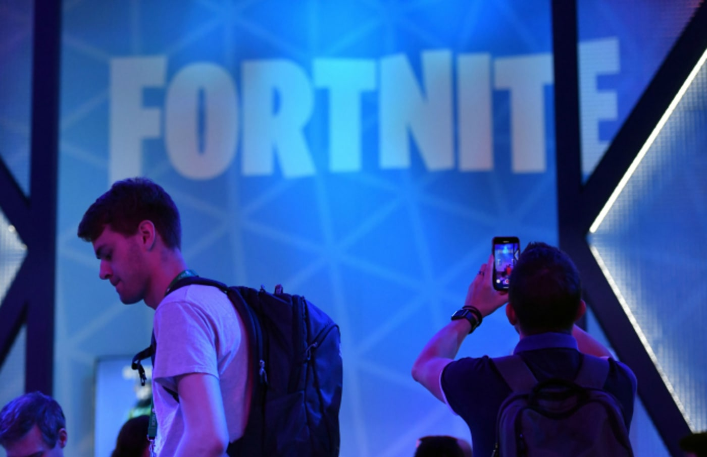 """A visitor takes pictures at the stand of the """"Fortnite"""" computer game"""