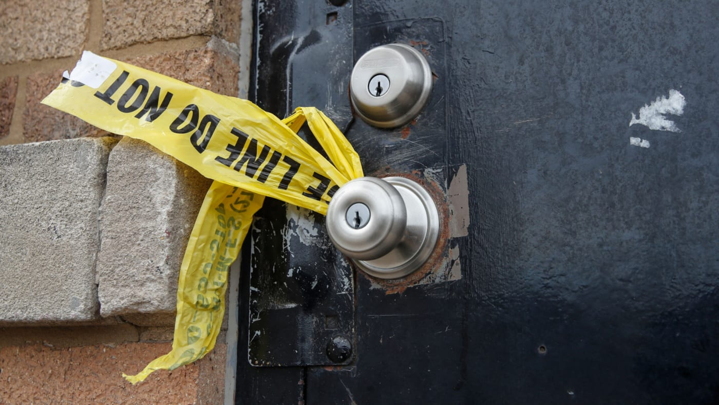 A piece of police caution tape is seen on the front door of the building where a shooting took place in Chicago.
