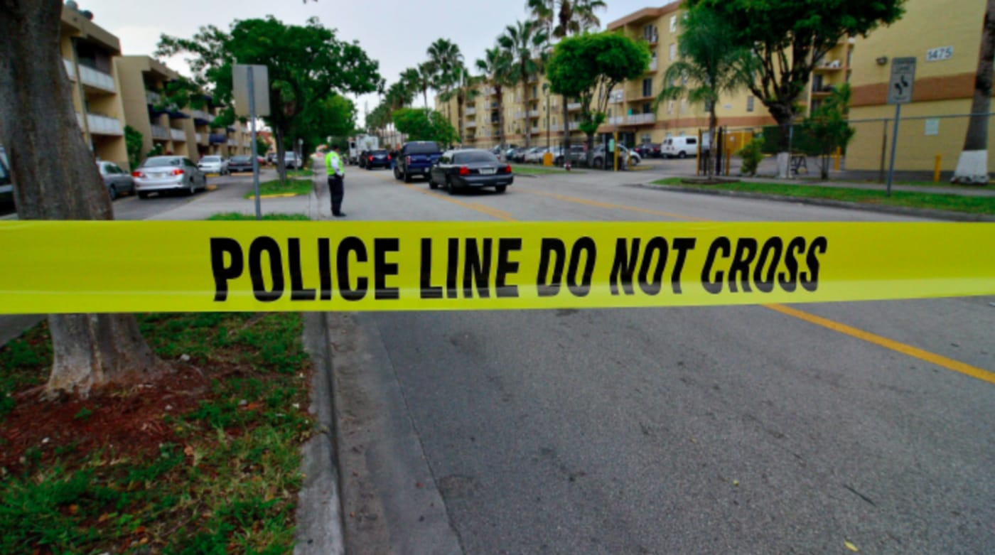 Police tape blocks the street to an apartment building