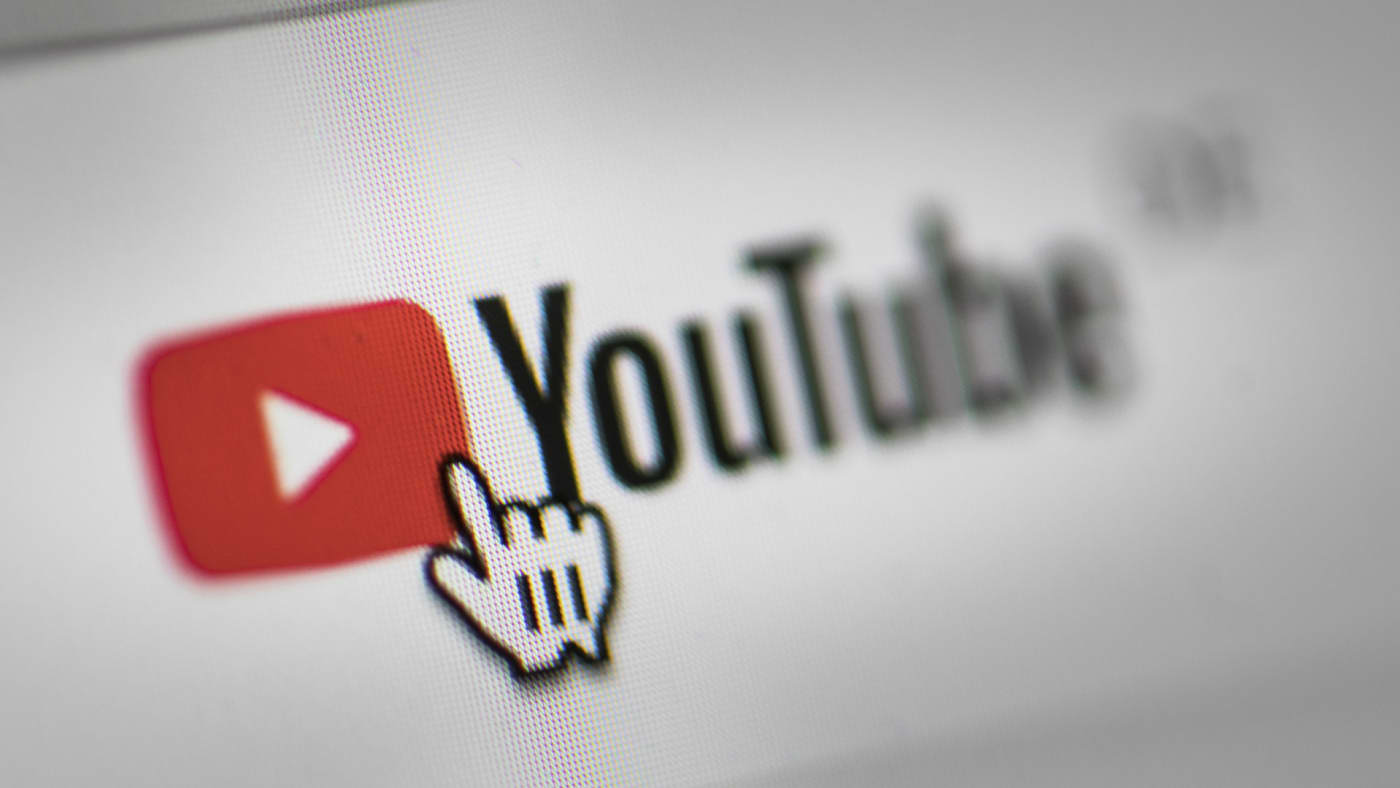 In this photo illustration the mouse cursor is pictured on the YouTube logo.