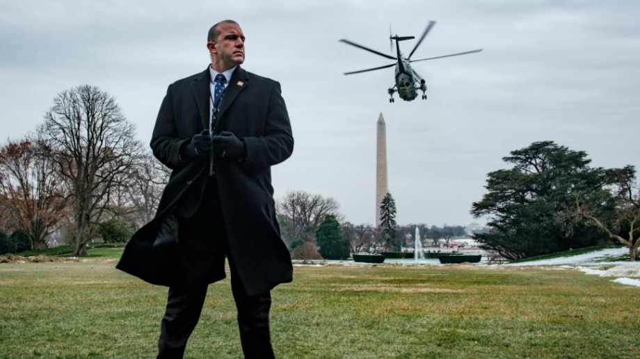A Secret Service agent stands watch as President Trump departs on Marine One