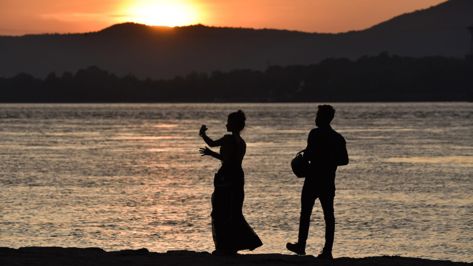 A couple takes selfie during sunset in banks of Brahmaputra river, in Guwahati, Assam, India.