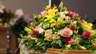 Flowers cover the coffins at the funeral of Noelene and Yvana Bischoff.