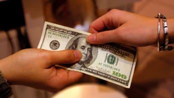 A shopper pays cash for sales merchandise.