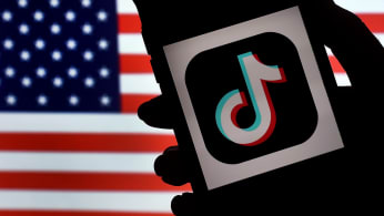 TikTok is displayed on the screen of an iPhone on an American flag background.