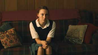 Saoirse Ronan sits on a plaid couch in Lady Bird.