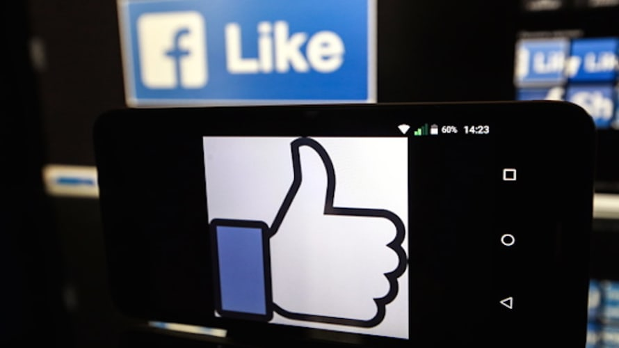 A Facebook thumbs-up sign on a smartphone screen.